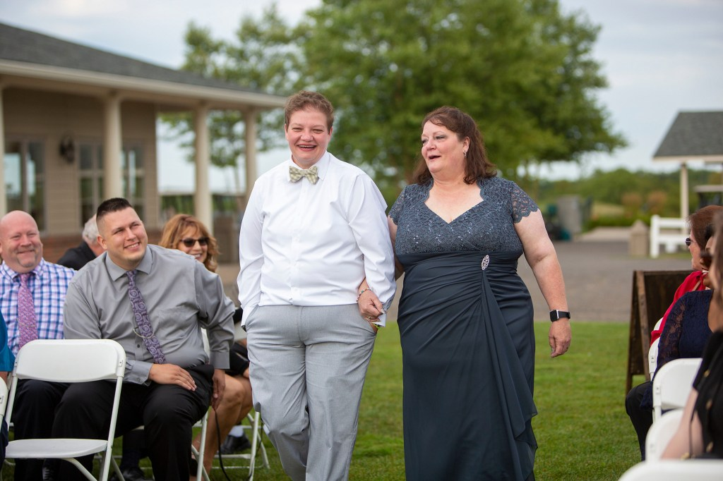 Daughter and mother share a laugh walking down the aisle