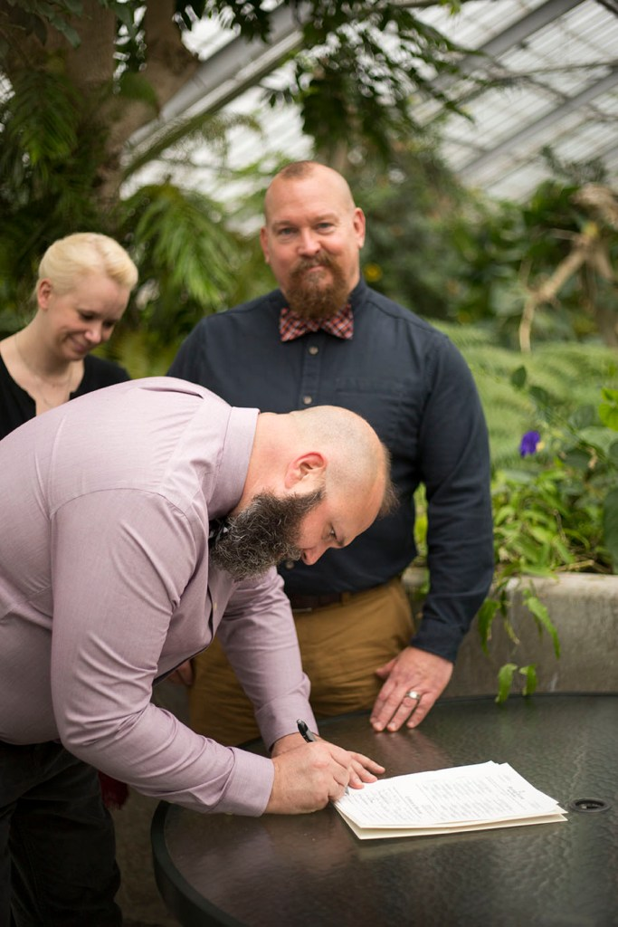 LGBTQ wedding couple signs marriage license at October wedding