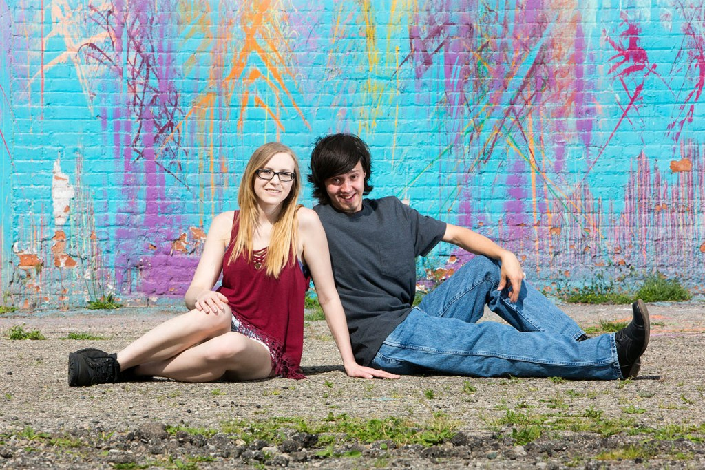 Couple sits in front of a mural for their Detroit urbex engagement session