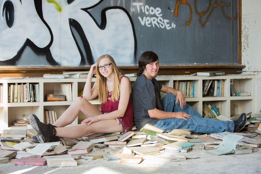 Engaged couple poses in the scattered books