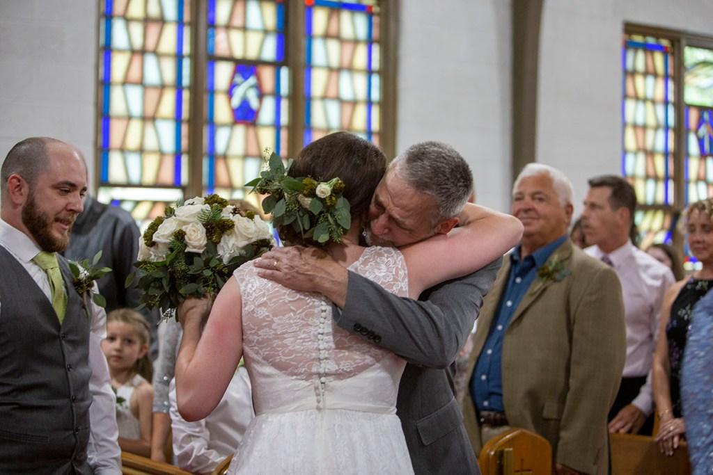 Father hugs bride as he hands her off