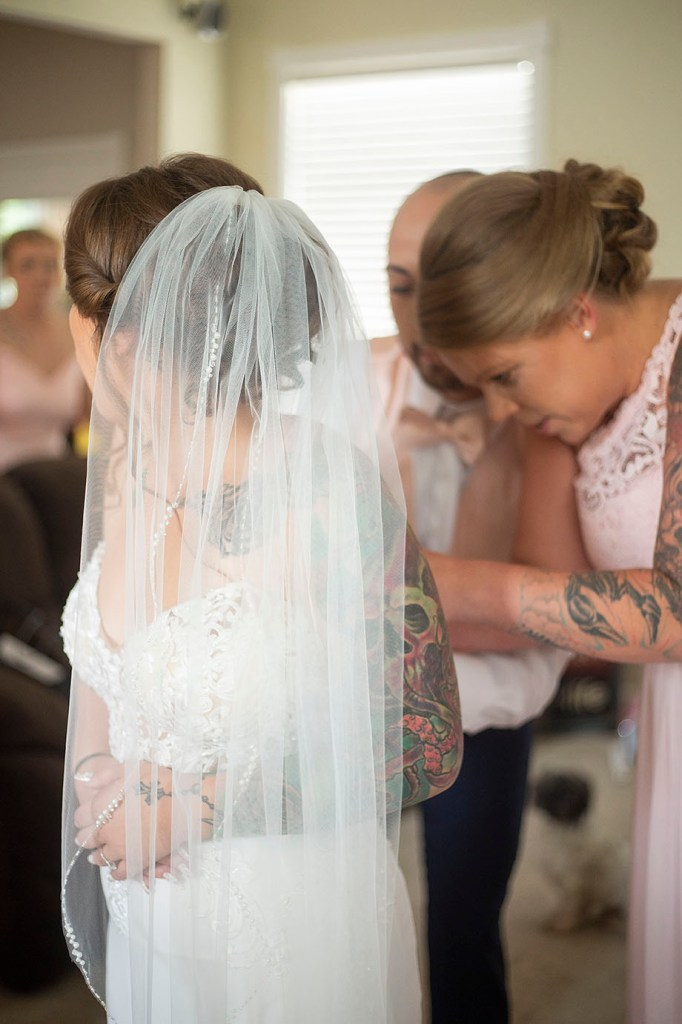 Amee getting zipped up in her wedding dress