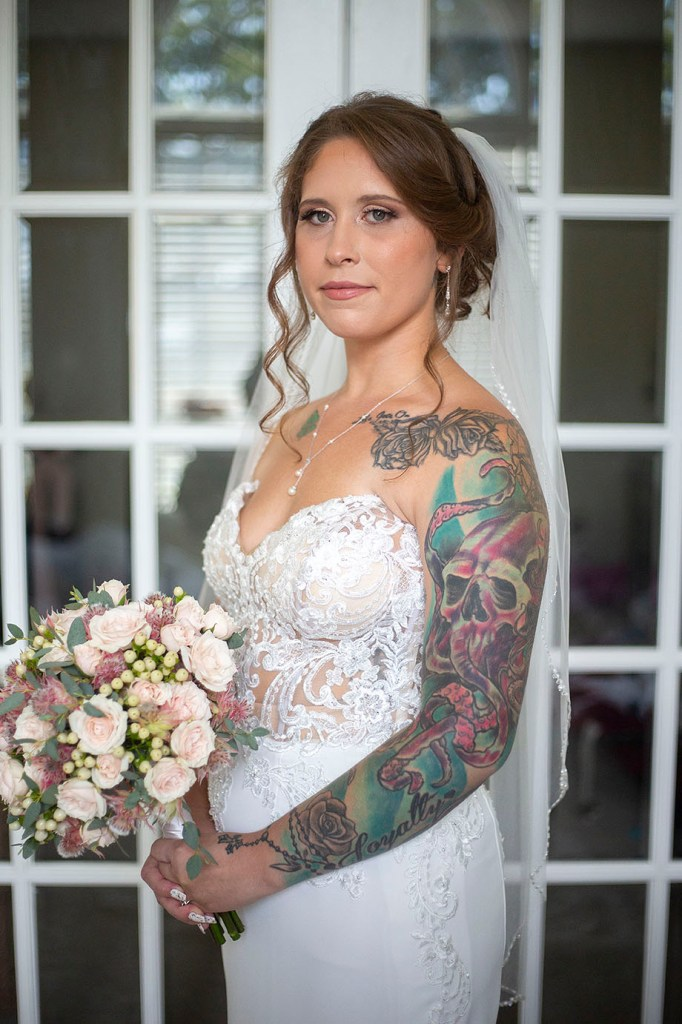 Bride poses in front of French doors