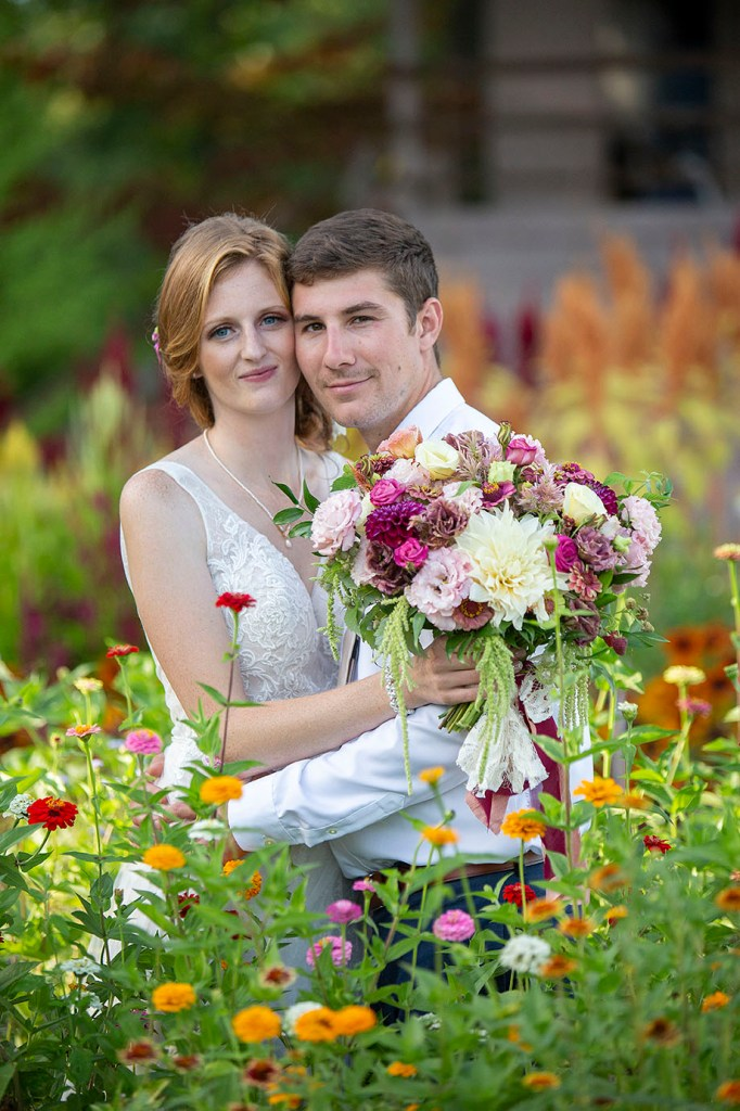 Carmen and Chris stand in the garden amongst the dahlias