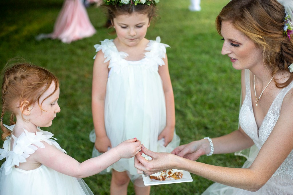 Bride sharing cake with her flower girls