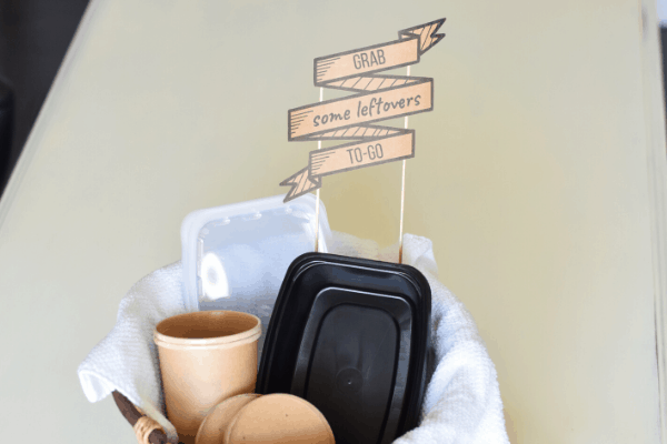 """leftover containers in a basket with a sign that reads """"grab some leftovers to go"""""""