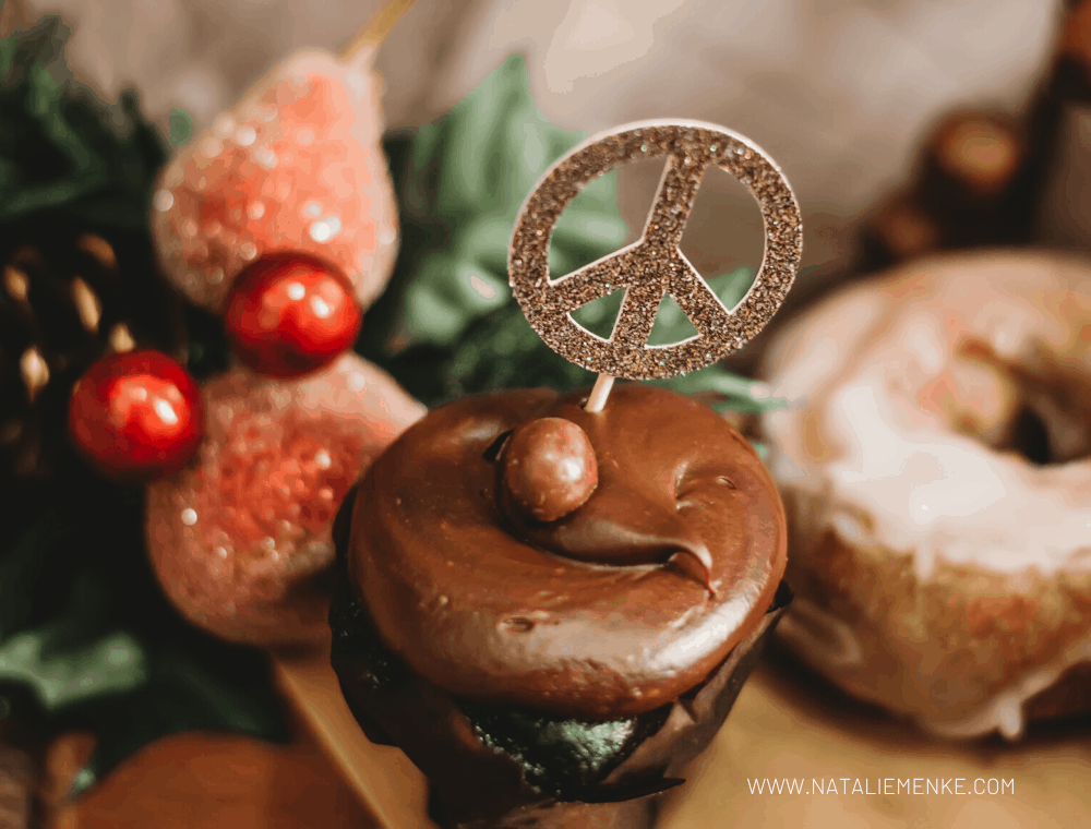 sparkly gold peace sign cupcake topper on a chocolate cupcake