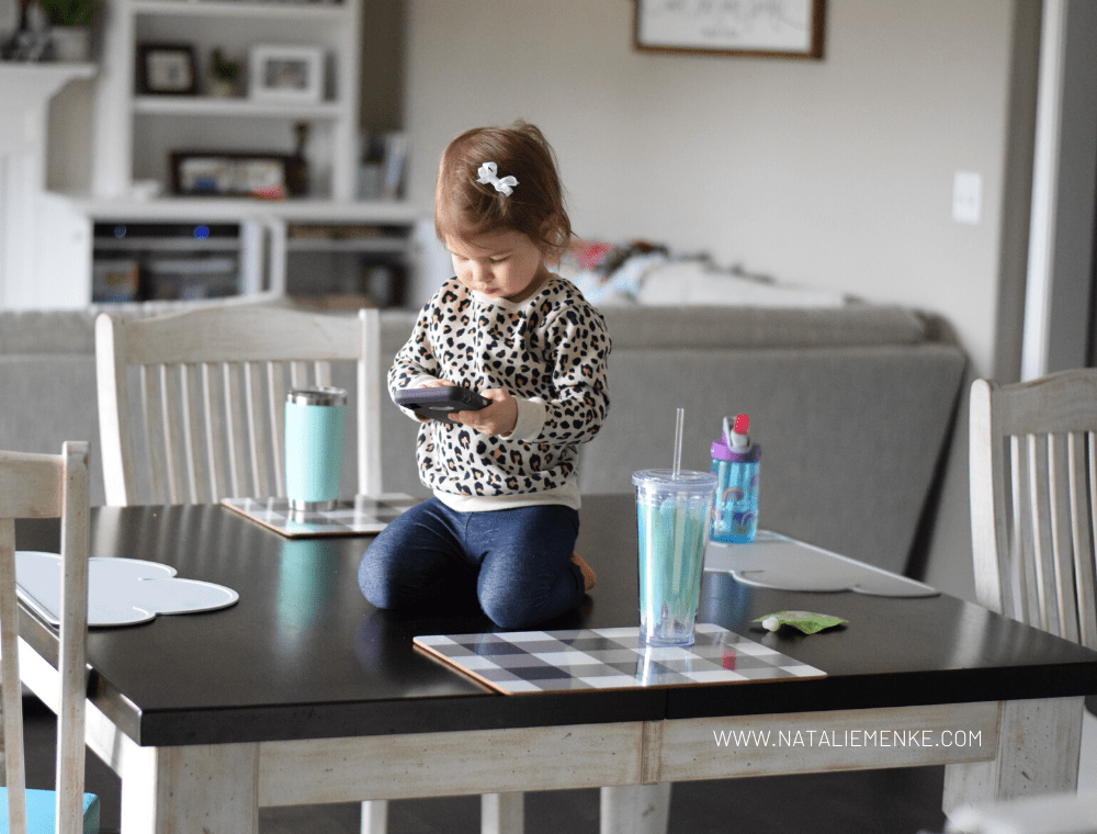 child sitting on top of a table while playing with an iPhone