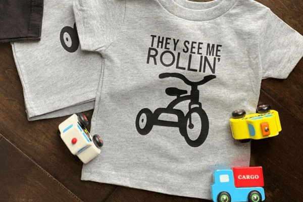 """gray toddler shirt with the text """"They see me rollin'"""" and an image of a tricycle"""