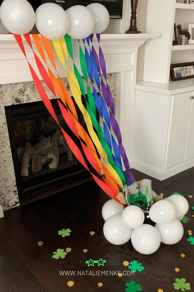 """Crepe paper rainbow party decorations with a pot of gold and white balloon """"clouds"""""""