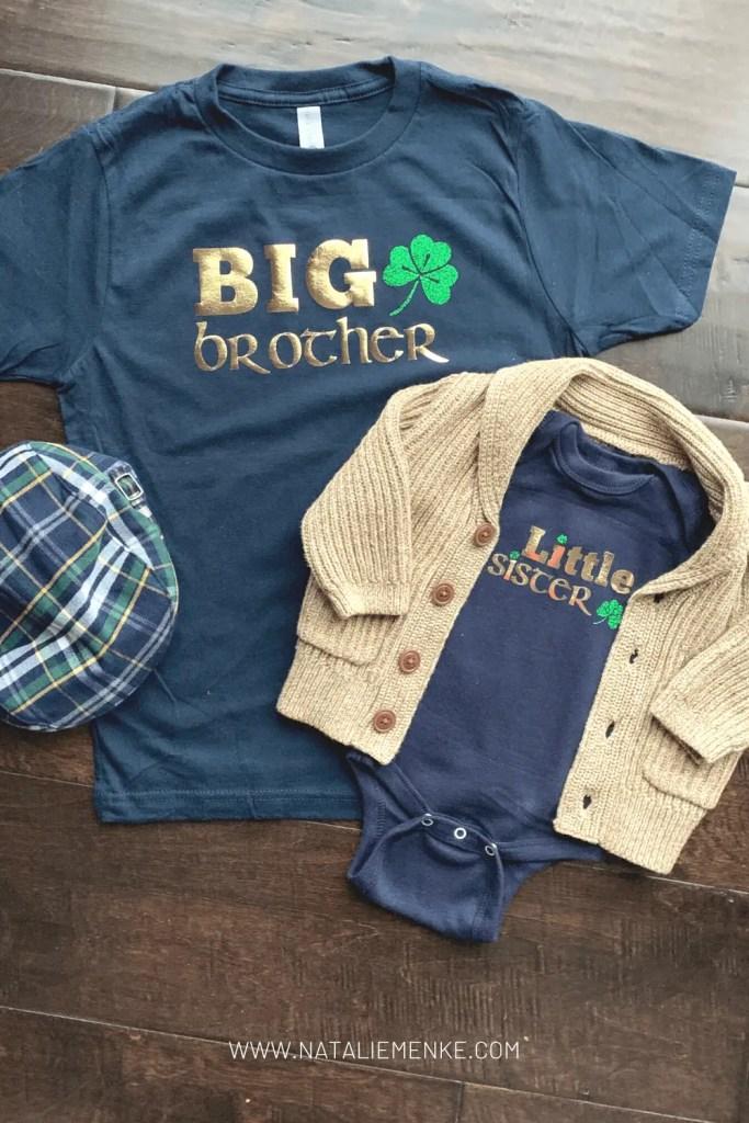 Navy and gold Irish-themed sibling shirt flatlay with green glitter shamrock decorations