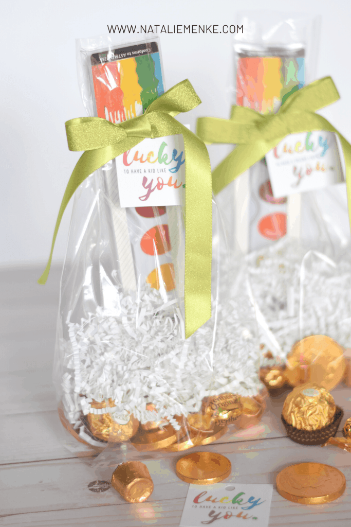 watercolor treat bag with 'lucky to a have kid like you' rainbow gift tag and chocolate candies with gold wrappers