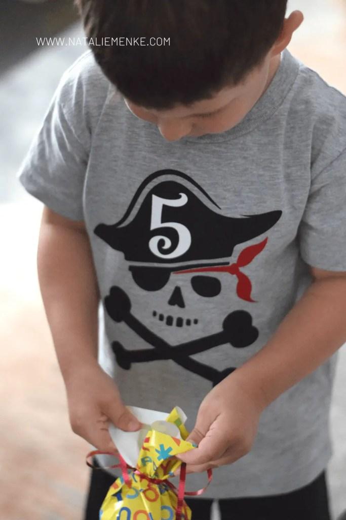 boy in a pirate birthday shirt opening birthday present