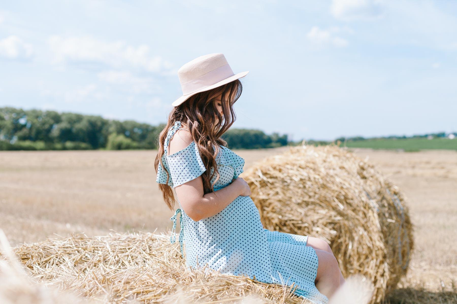 Беременная девушка в голубом платье сидит на стоге сена