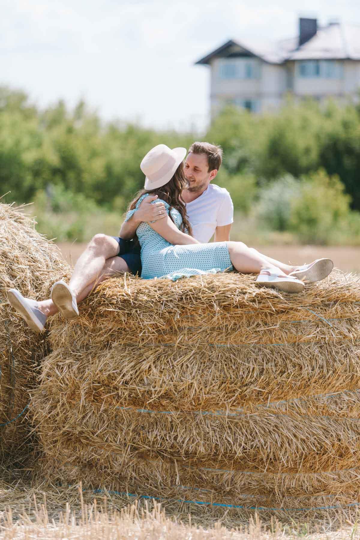 Очень большой сноп сена на котором вместились беременная девушка с её мужем для фотосессии