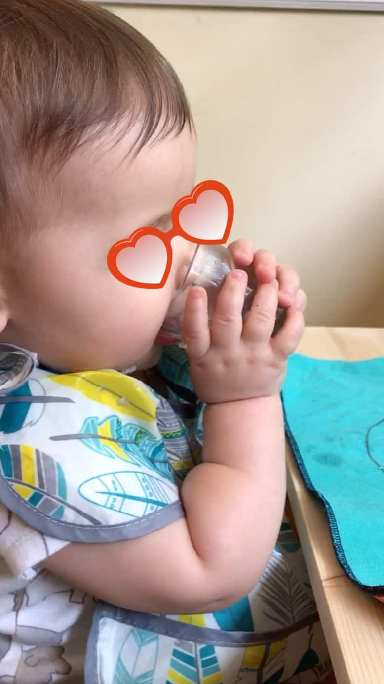 Montessori baby using a tiny glass