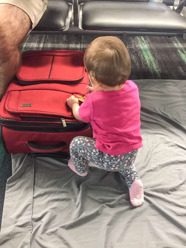 baby playing on airport floor on a bedsheet
