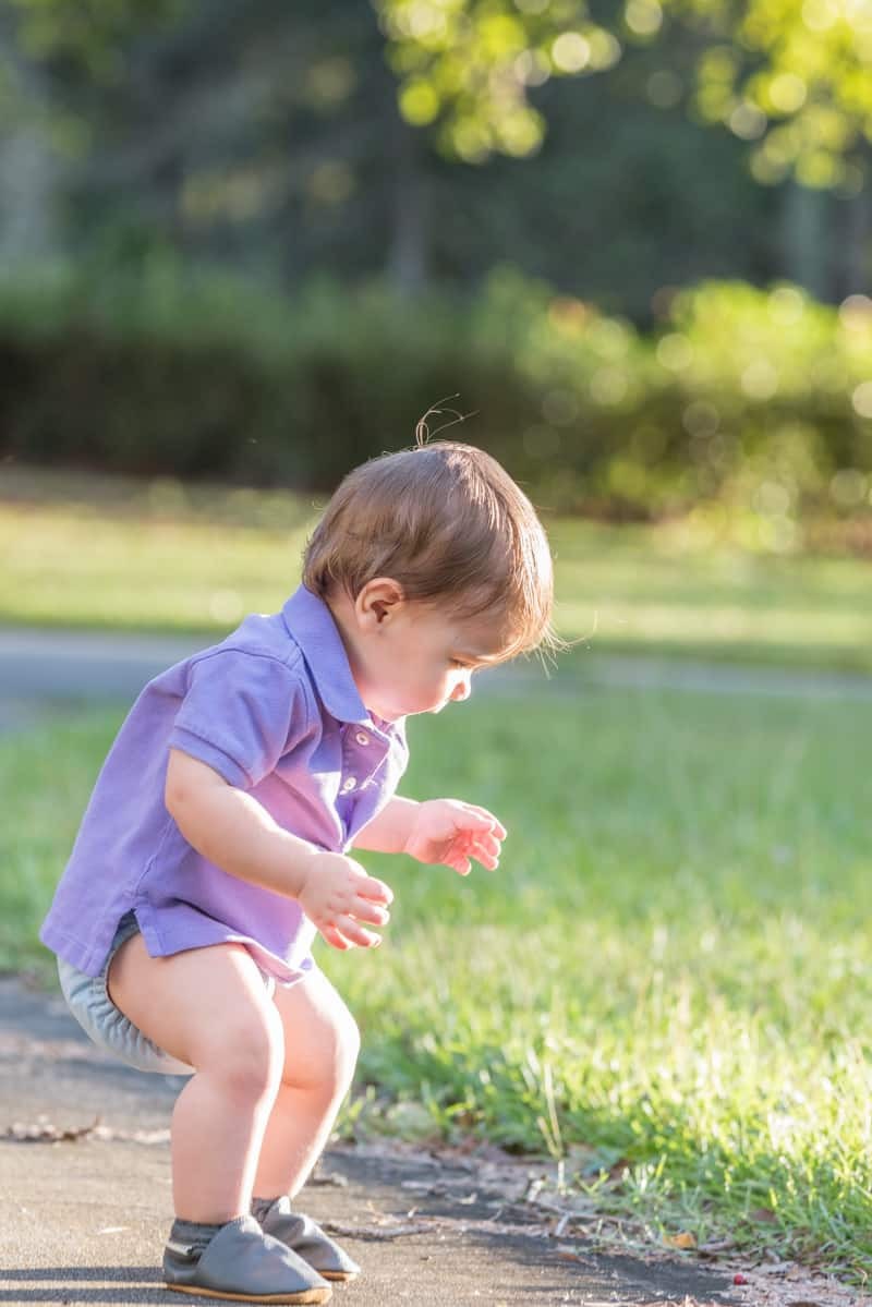 toddler playing in grass