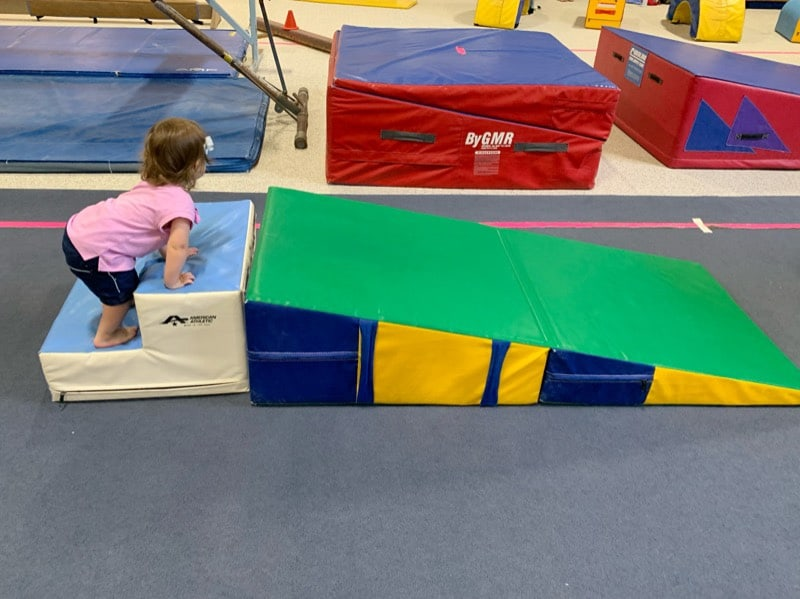 toddler on foam wedge at gymnastics
