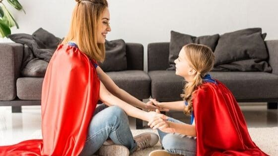 mom and daughter wearing superhero capes