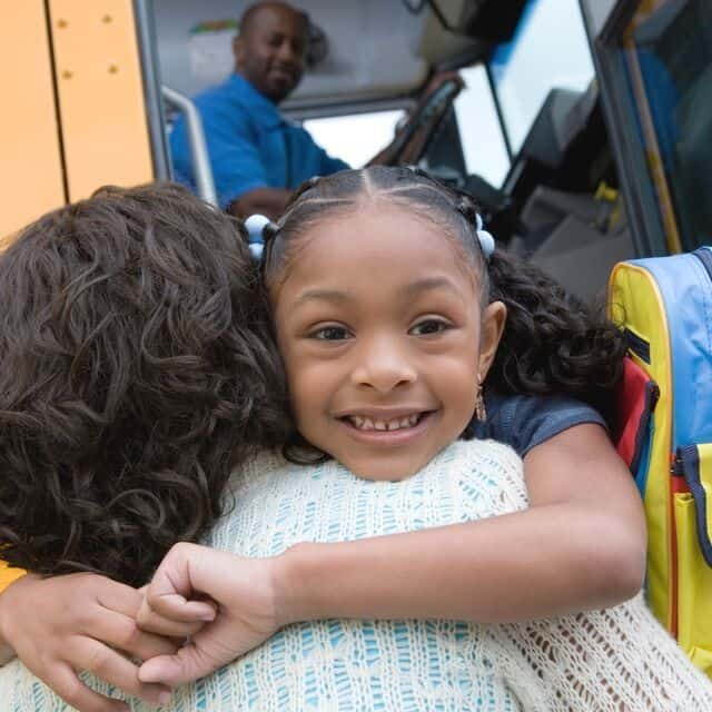 smiling girl hugging mom by school bus