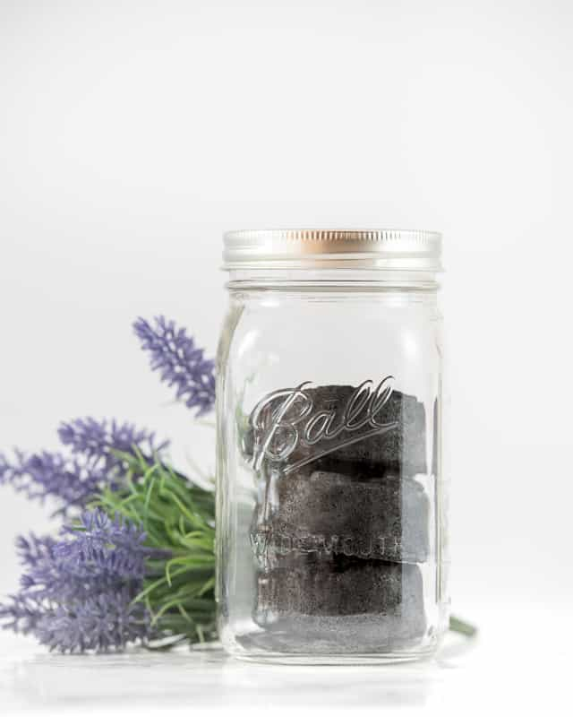 three black bath bombs with activated charcoal in a mason jar