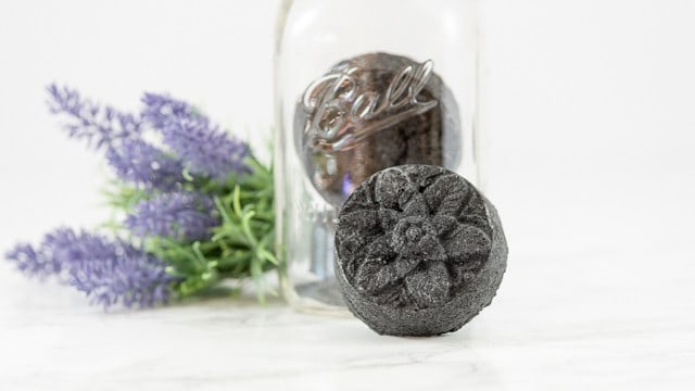 a shot of a black back bomb made with activated charcoal leaning against a jar holding two more bath bombs. There are springs of lavender out of focus behind the bath bombs.