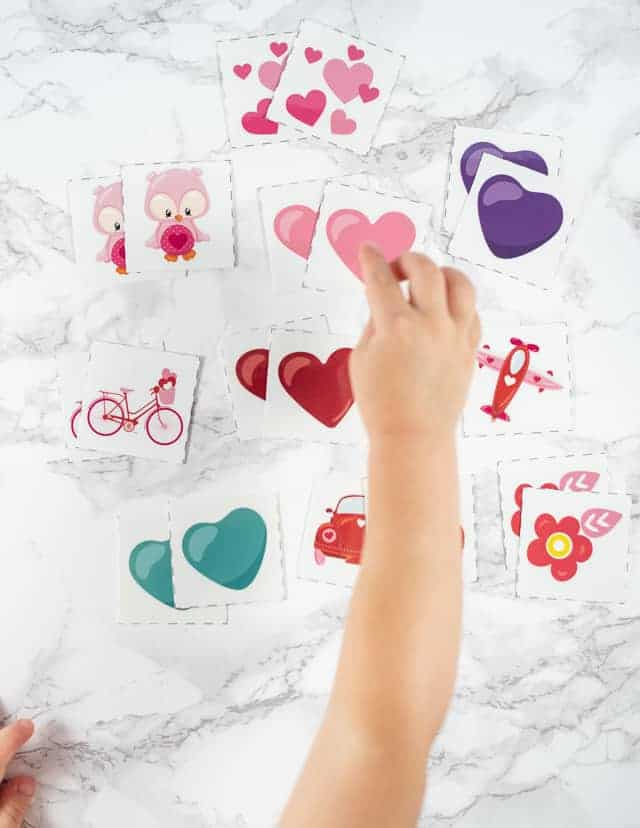 A toddler's hand reaching for a pink heart in a set of Valentine's Day matching game cards