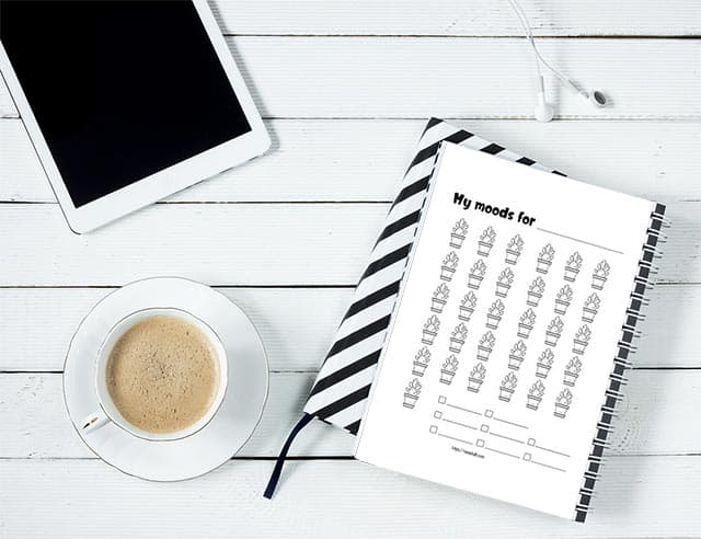 A cactus mood tracker printable in a spiral notebook. It is next to a cup of coffee and a tablet on a white wood table.