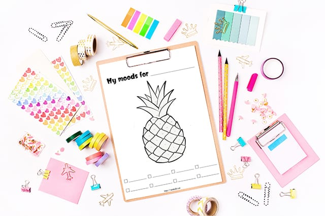 Printable pineapple mood tracker on a clipboard surrounded by pink and tea stationary and office supplies