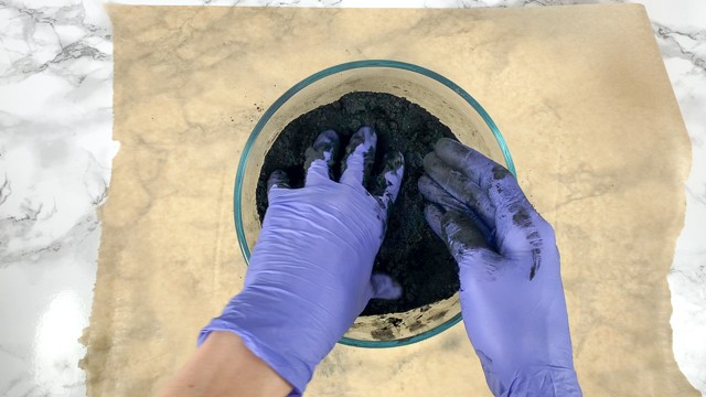 Kneading black bath bomb mixture with gloved hands