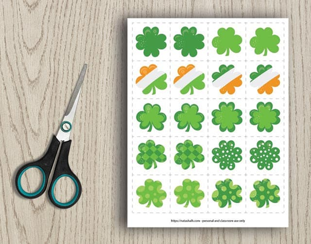 printable shamrock matching card game with 10 different shamrock images on a wood background next to scissors