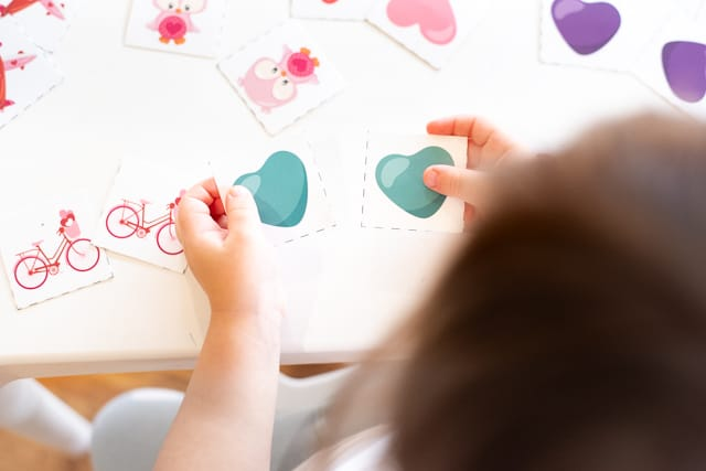 A toddler holding two teal heart cards from a Valentine's Day matching game printable set
