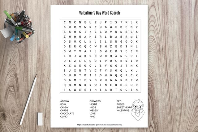 Printable Valentine's Day word search on a wood background with a cup of pens and a pencil