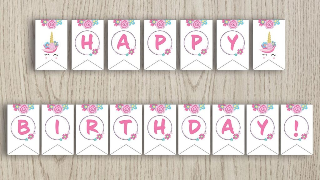 Free printable happy birthday banner with pink flowers and unicorns. The banner is shown on a wood background.