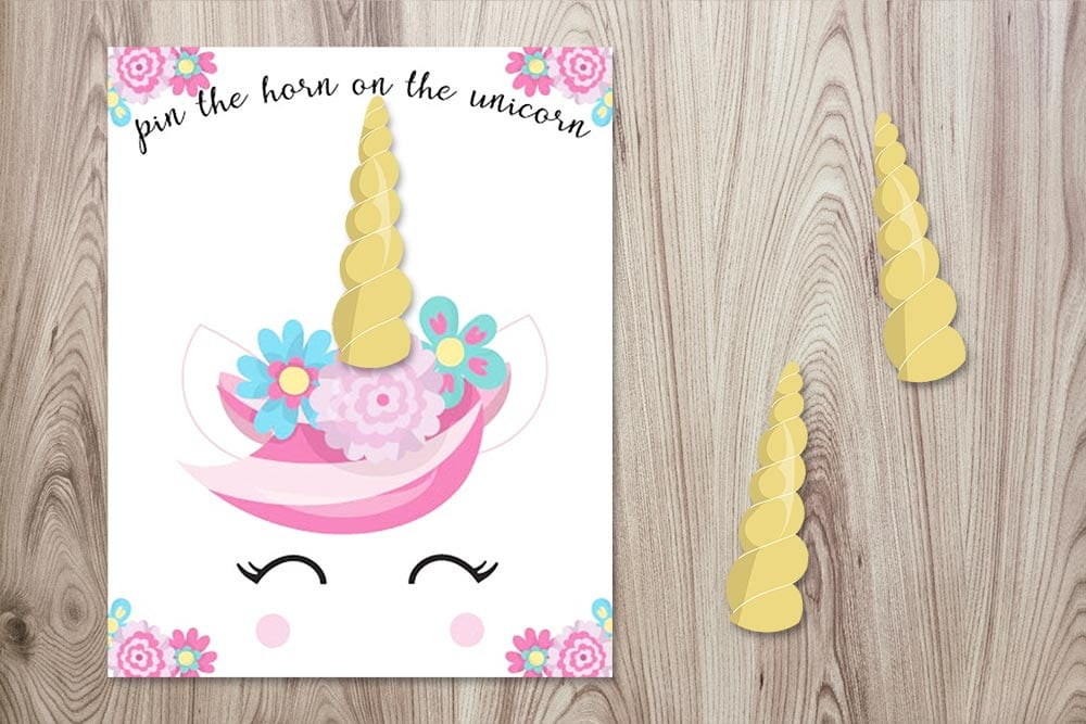 free printable pin the horn on the unicorn poster with three horns on a wood background