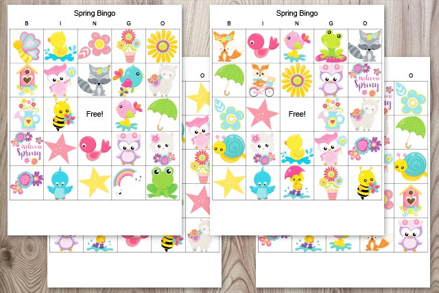 four free printable picture bingo cards for spring on a wood background. The bingo cards feature cartoon images like foxes, birds, frogs, and flowers