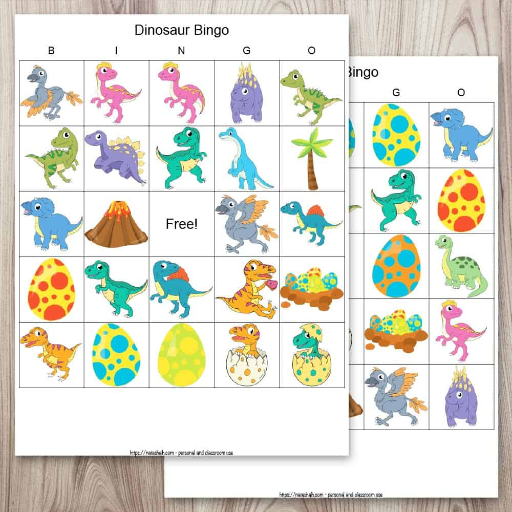Two free printable dinosaur picture bingo cards on a wood background