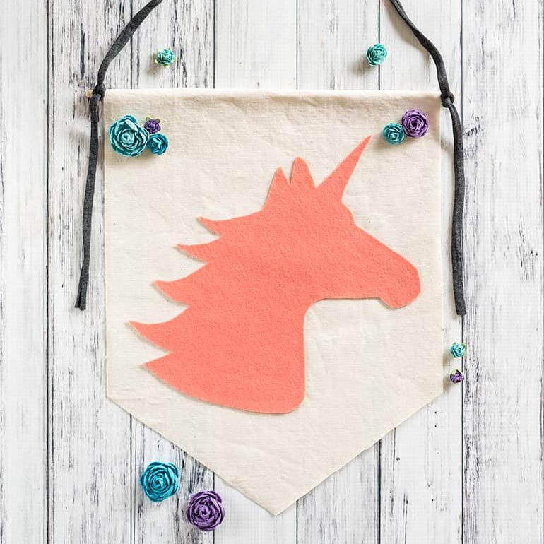 no-sew felt unicorn banner on a white background with paper flowers.