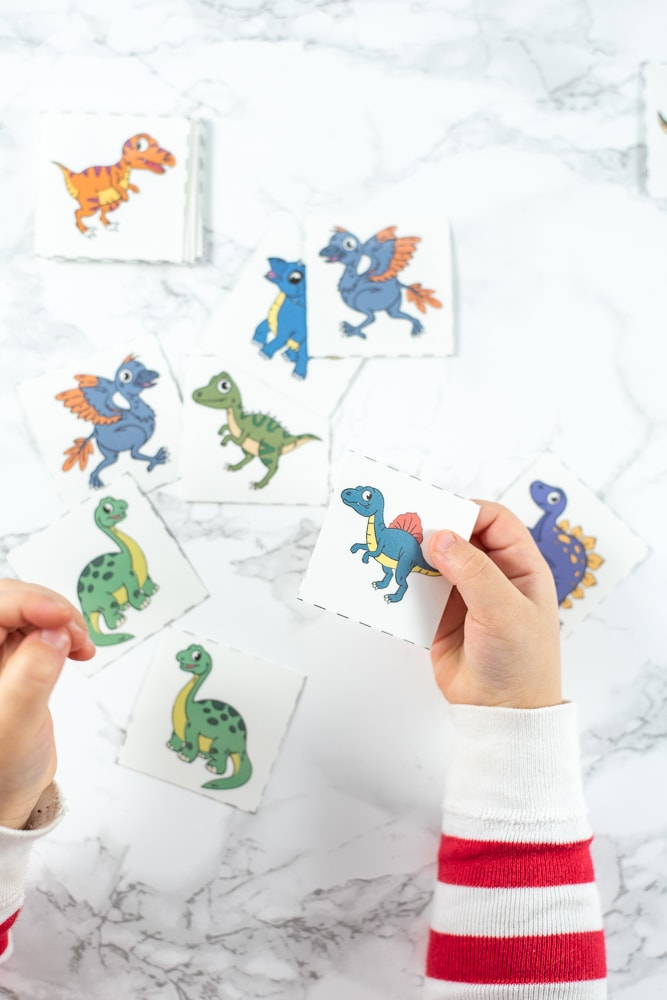 A toddler playing with a matching game featuring mirror image pairs of cartoon dinosaurs. She is holding a green brachiosaurus and a spinosaurus in her hands. Only her hands and arms, in red and white striped pajamas, are visible, not the rest of her body. In the background there are more dinosaur matching cards on a white faux marble surface.