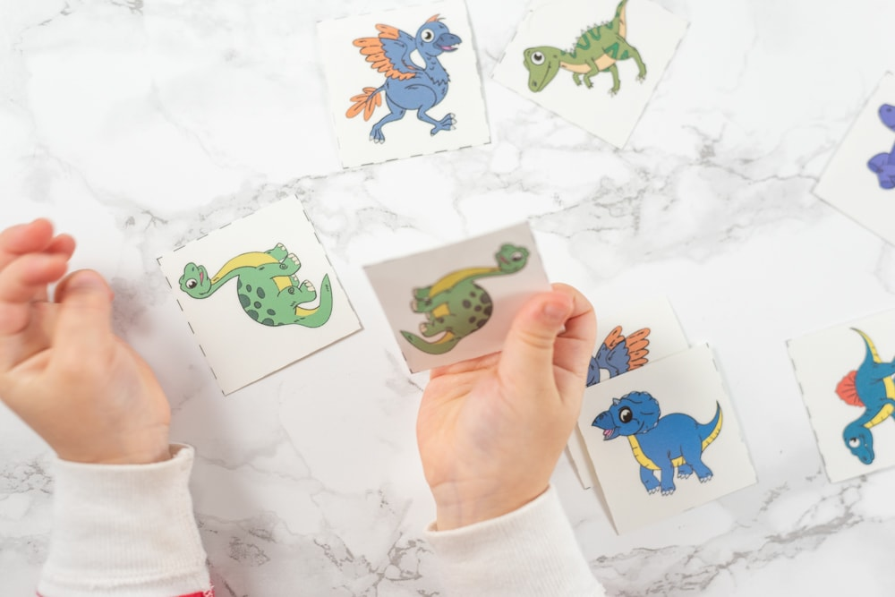 Toddler playing with dinosaur matching card printable game
