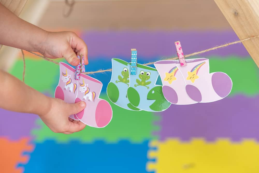 a toddler unclipping a pair of printable unicorn socks from a piece of twine. The socks are hanging on a limeade from twine with two more pairs of printable socks from a printable sock matching game. The other pairs of socks are green with frogs and pink with stars, respectively. The toddler's hands and arms are in frame.