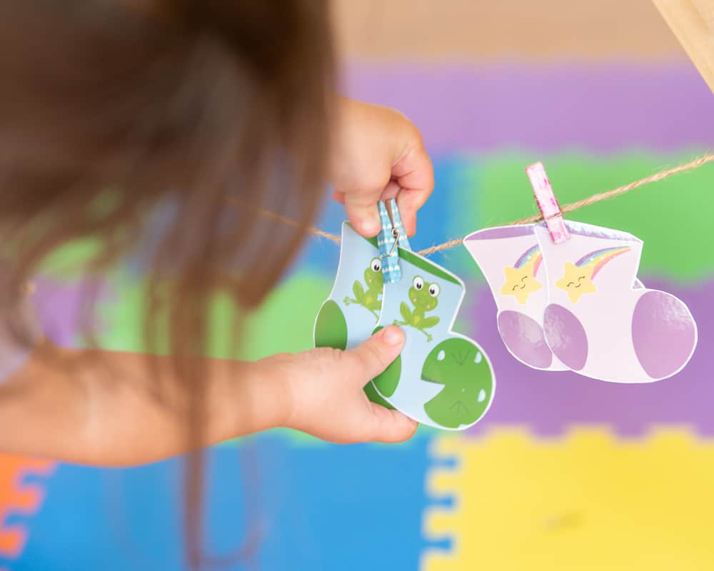 a toddler playing with a pair of printable socks for a matching game. She is unclipping a small clothespin holding them on a line.