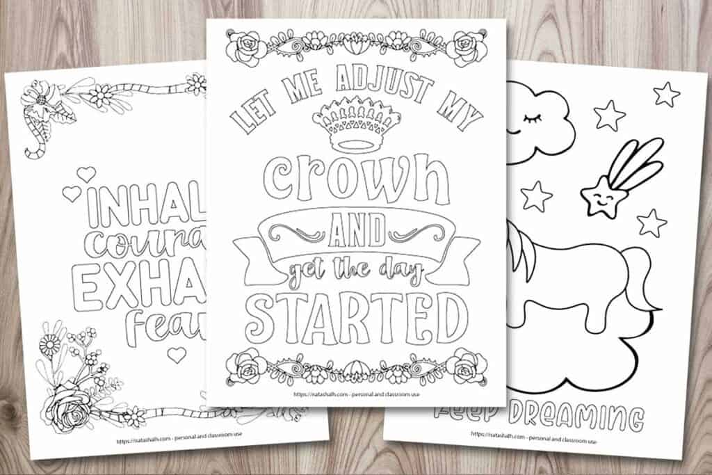 "A mockup of three inspirational quote coloring pages on a wood background. The center page has a crown and the text ""let me adjust my crown and get the day started."" Behind it and to the left is a coloring page with a floral border and the text ""inhale courage, exhale fear."" On the right is a coloring page with a cartoon unicorn standing on a cloud and the text ""keep dreaming"""