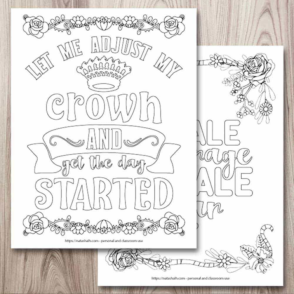 "A mockup of two printable inspirational quote coloring pages on a wood background. In the top left is a page with a crown, a floral border, and the text ""let me adjust my crown and get the day started."" Behind this page, and partially obscured, is a page with a floral border and the text ""inhale courage exhale fear"""