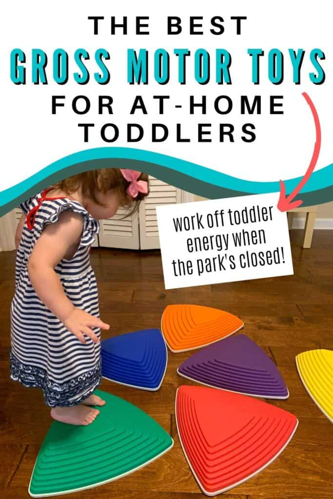 "Text ""the best gross motor toys for at-home toddlers"" There is an arrow pointing at additional text ""work off toddler energy when the park's closed!"" Below the text is a picture of a young toddler in a blue and white striped dress using plastic stepping stones on a wood floor."