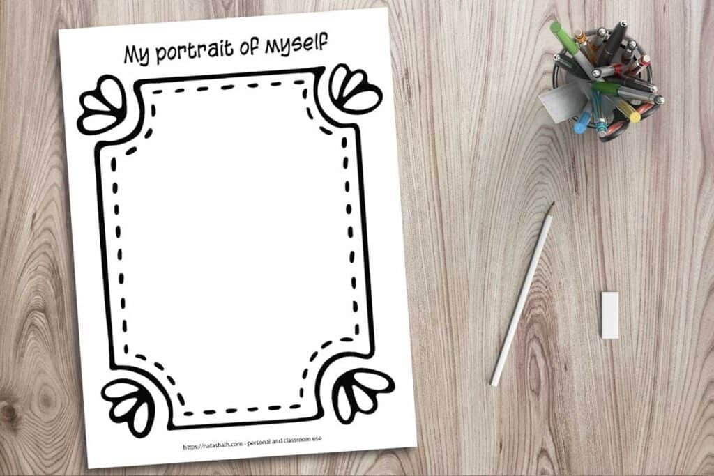 """A printable worksheet mockup on a wood background with a cup of colorful pens, a pencil, and an eraser. The worksheet says """"a portrait of myself"""" across the top and has a large hand drawn frame around the edge of the page"""