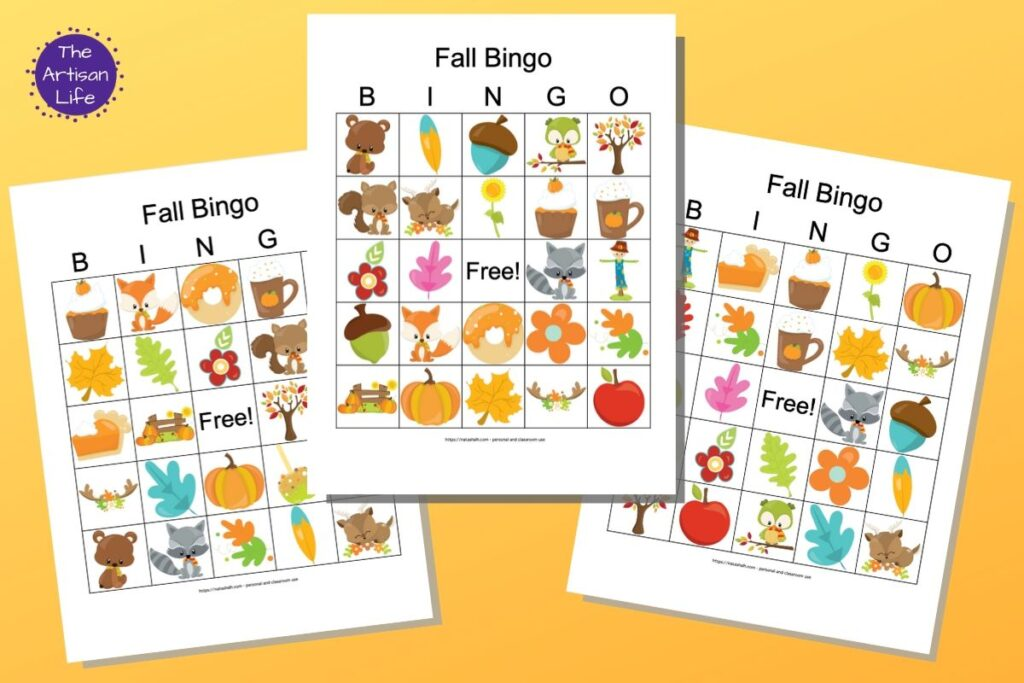 "Three free printable fall bingo cards featuring cartoon fall images. The bingo card previews are on a colorful background with a yellow to orange gradient. In the top left is a purple circle with the white text ""The Artisan Life"""