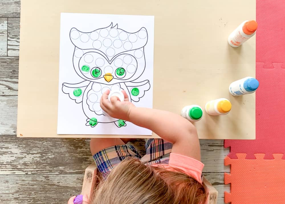 a top down shot of a toddler coloring an owl do a dot marker page