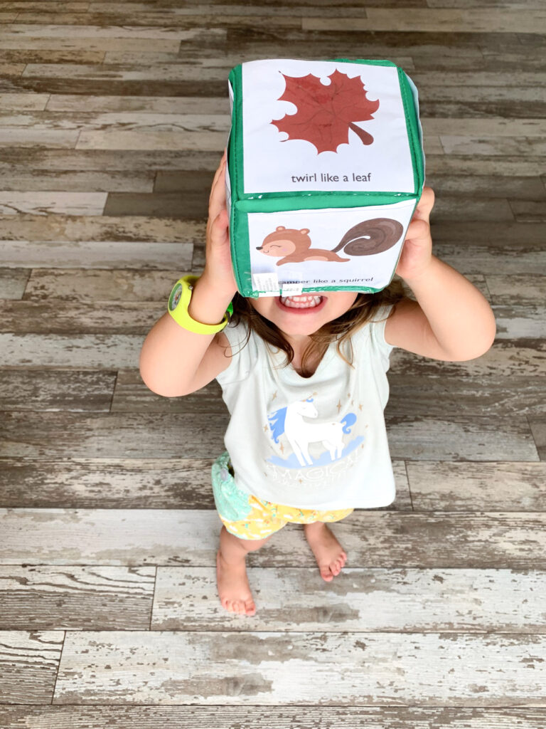 "A toddler holding up a differentiated instruction cube with fall themed gross motor movement cards. The top card says ""twirl like a leaf"". The toddler is wearing a unicorn shirt and a green watch."